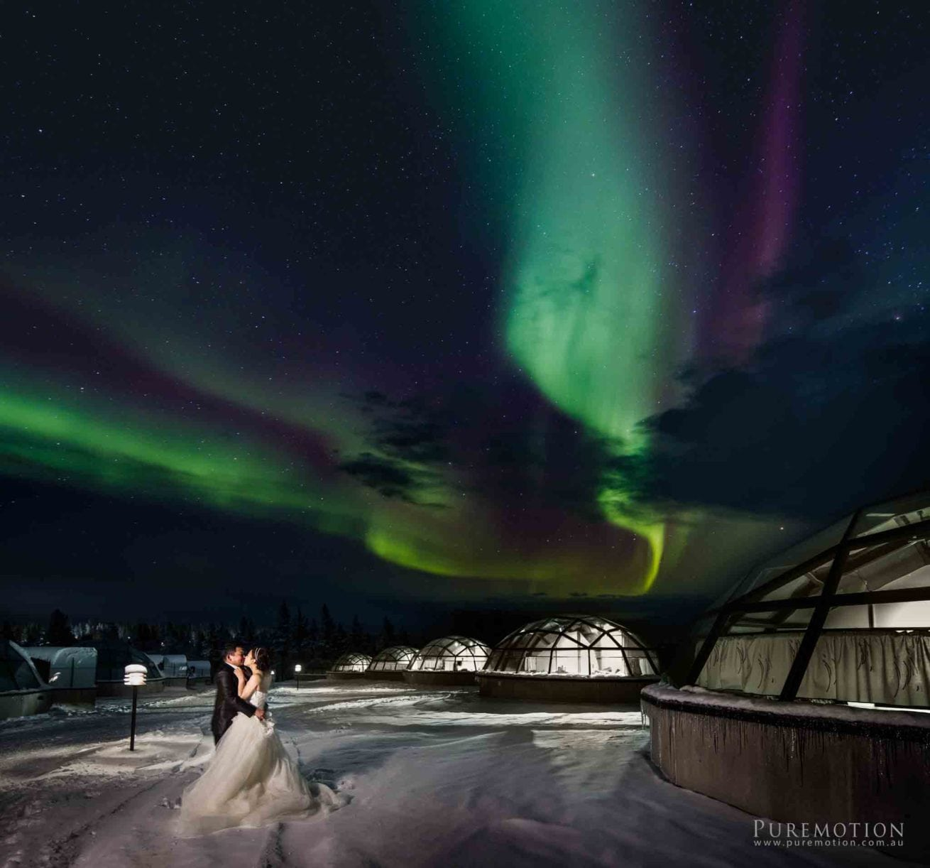 Aura lights for married couple in Iceland next to Igloos